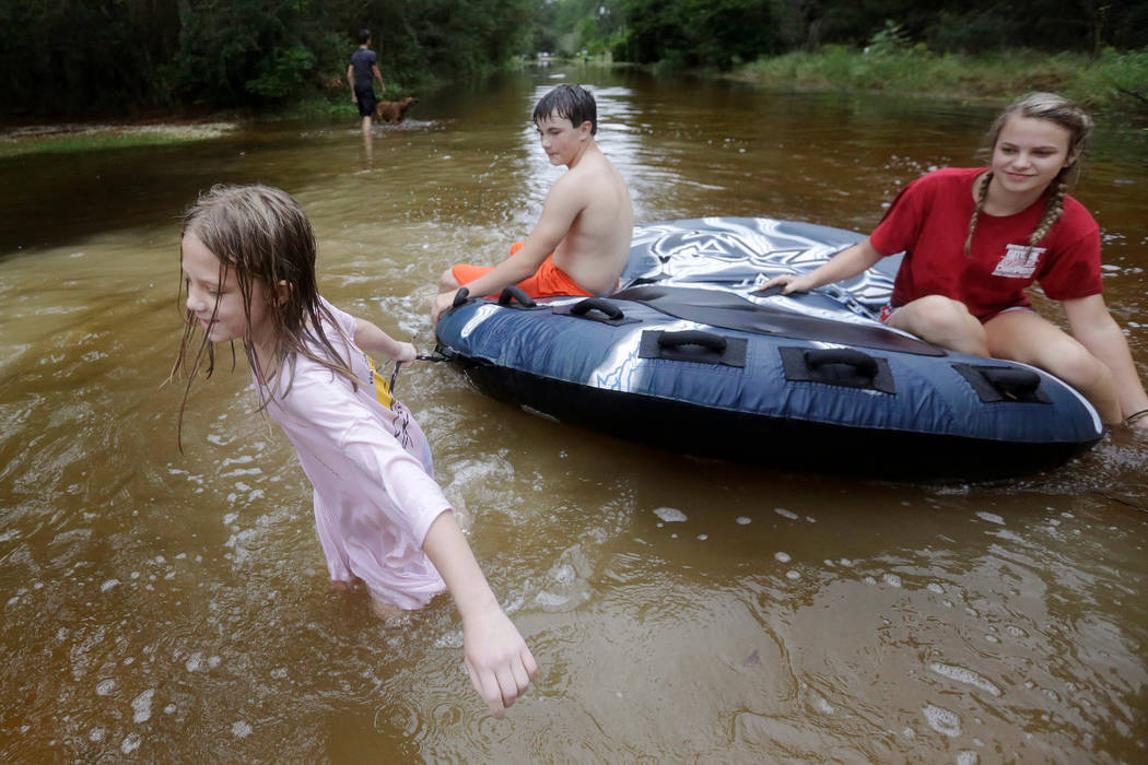 Crimson Peters, 7, left, Tracy Neilsen, 13, center, and Macee Nelson, 15, ride in an inner tube down a flooded street after Hurricane Nate, Sunday, Oct. 8, 2017, in Coden, Ala. (AP Photo/Brynn And ...