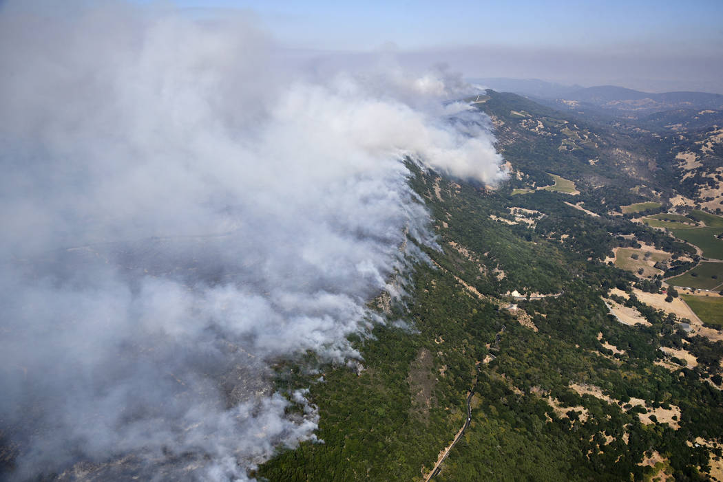 Smoke rises as a wildfire burns in the hills east of Napa, Calif., Monday, Oct. 9, 2017. Wildfires whipped by powerful winds swept through Northern California sending residents on a headlong fligh ...