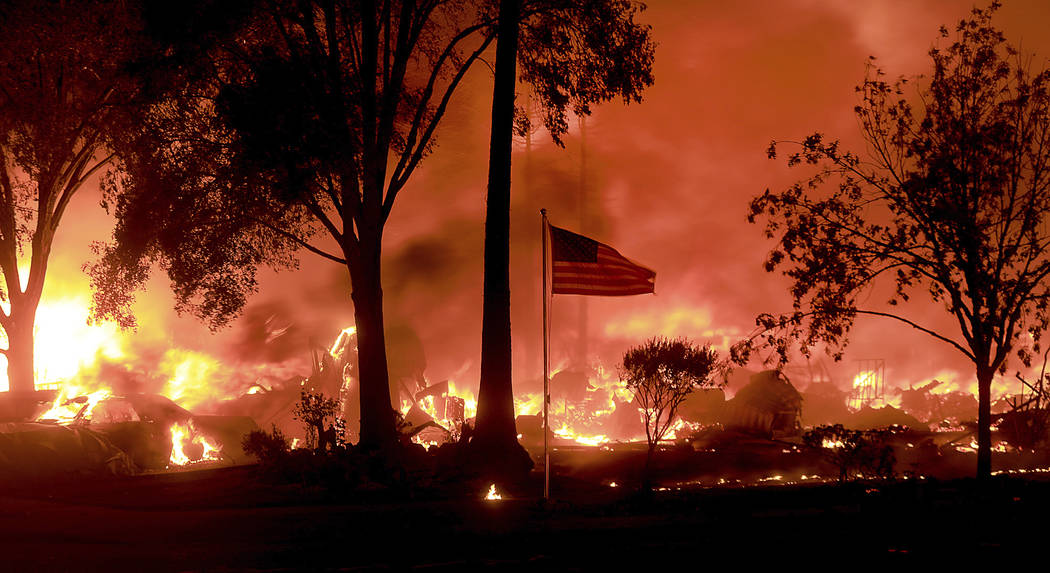 An American flag still fly's as as structures burn in Coffey Park, Monday Oct. 9, 2017. More than a dozen wildfires whipped by powerful winds been burning though California wine country. The flame ...