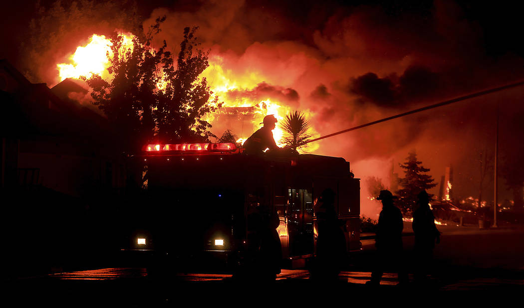 Gold Fidge firefighters use a deck gun to protect structures in Coffey Park in Santa Rosa, Calif., Monday Oct. 9, 2017. More than a dozen wildfires whipped by powerful winds been burning though Ca ...
