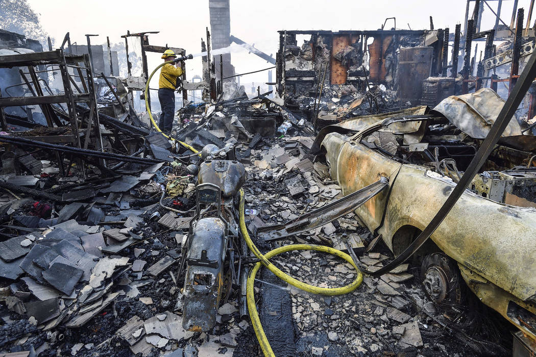 A firefighter puts out hot spots in a home that was destroyed by a wildfire in Anaheim Hills in Anaheim, Calif., Monday, Oct. 9, 2017. (Jeff Gritchen/The Orange County Register via AP)