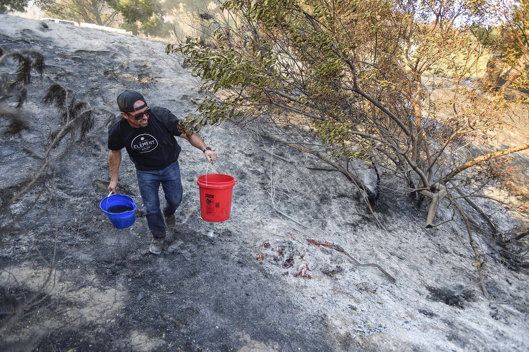 Brandon Zimprich looks for hot spots as he walks along the hillside off East Avenida de Santiago in Anaheim, Calif., Monday, Oct. 9, 2017. Wildfires whipped by powerful winds swept through Norther ...