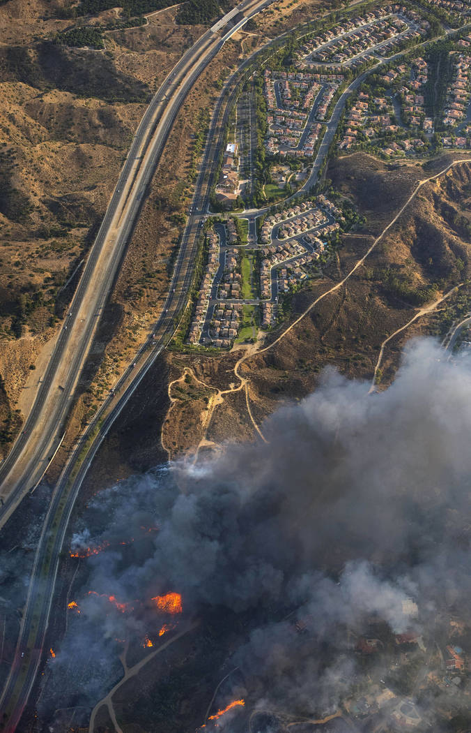 A wildfire moves closer to North Tustin homes along the 261 freeway in Tustin, Calif., Monday, Oct. 9, 2017. Deadly wildfires whipped by powerful winds swept through California wine country Monday ...