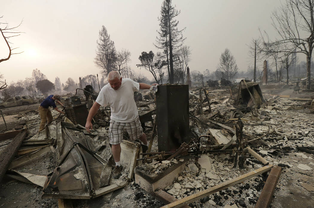 Mark Pedersen and his son Ben, left, look through the remains of their home destroyed by fires in Santa Rosa, Calif., Monday, Oct. 9, 2017. (AP Photo/Jeff Chiu)