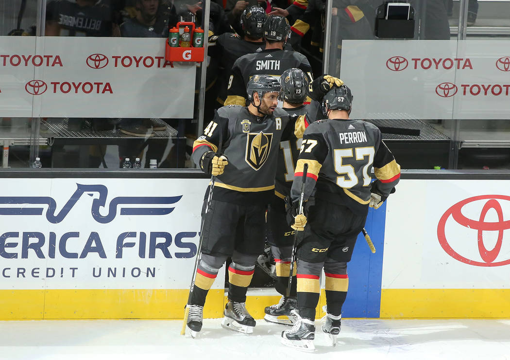 Vegas Golden Knights left wing Pierre-Edouard Bellemare (41) places his hand on top of Vegas Golden Knights left wing David Perron's (57) head after Perron's game winning goal at T-Mobile Arena in ...