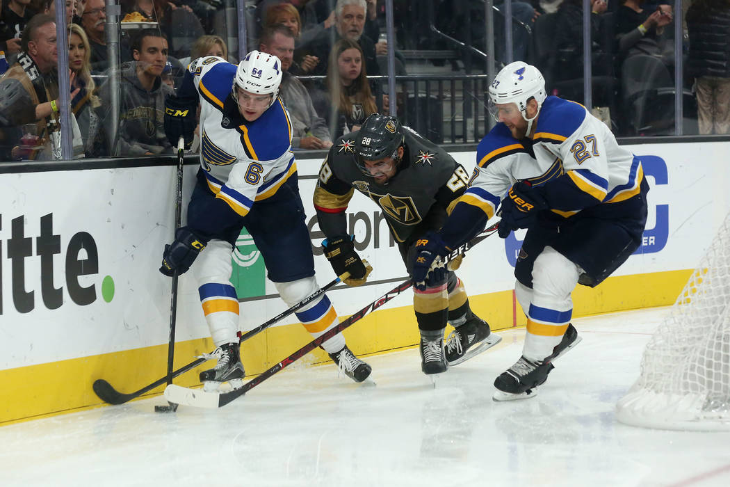 St. Louis Blues left wing Sammy Blais (64), Vegas Golden Knights left wing William Carrier (28) and St. Louis Blues defenseman Alex Pietrangelo (27) fight for the puck during a game at T-Mobile Ar ...