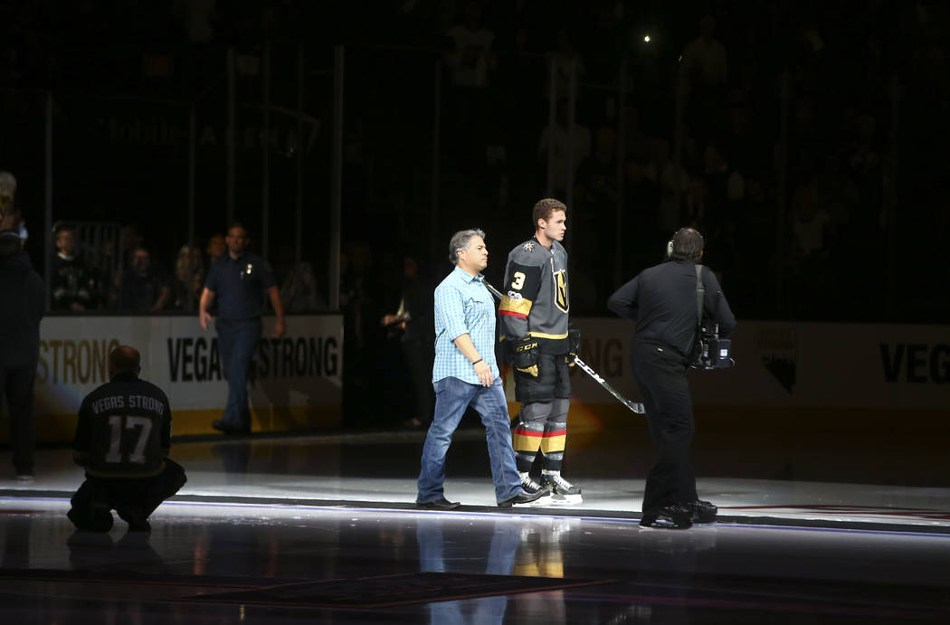 Vegas Golden Knights' Brayden McNabb (3) is introduced with a first responder before playing the Arizona Coyotes in an NHL hockey game at T-Mobile Arena in Las Vegas on Tuesday, Oct. 10, 2017. Cha ...