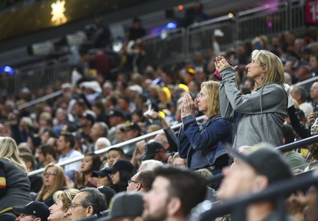 Fans cheer for first responders and victims of the mass shooting in Las Vegas before the start of an NHL hockey game at T-Mobile Arena between Golden Knights and Arizona Coyotes on Tuesday, Oct. 1 ...
