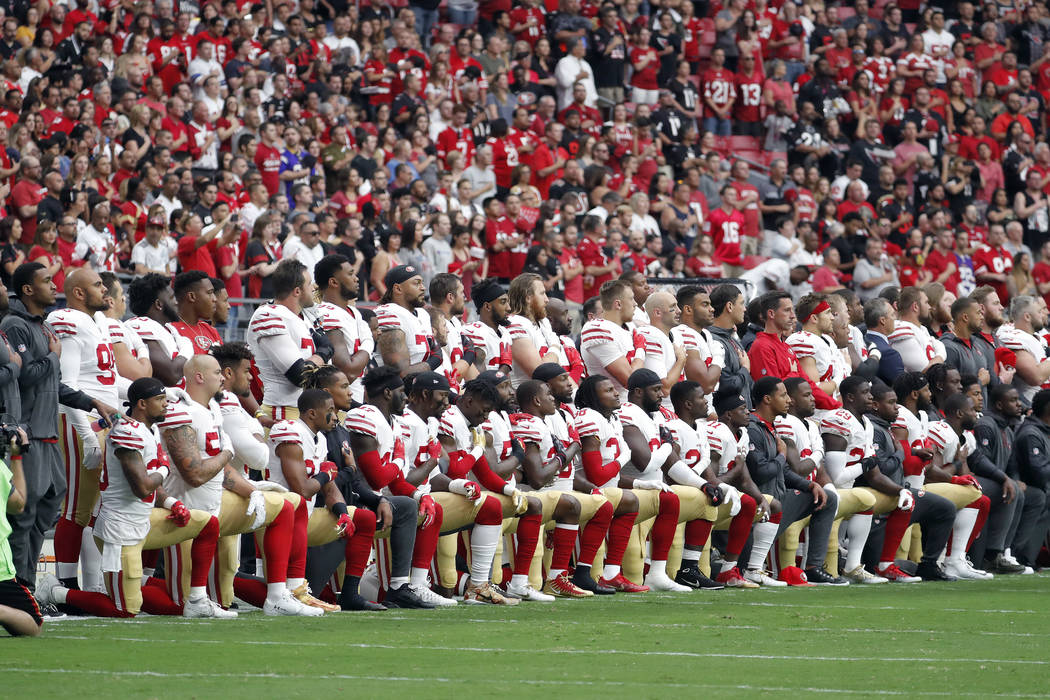 Members of the San Francisco 49ers kneel during the national anthem as others stand during the first half of an NFL football game against the Arizona Cardinals, Sunday, Oct. 1, 2017, in Glendale,  ...