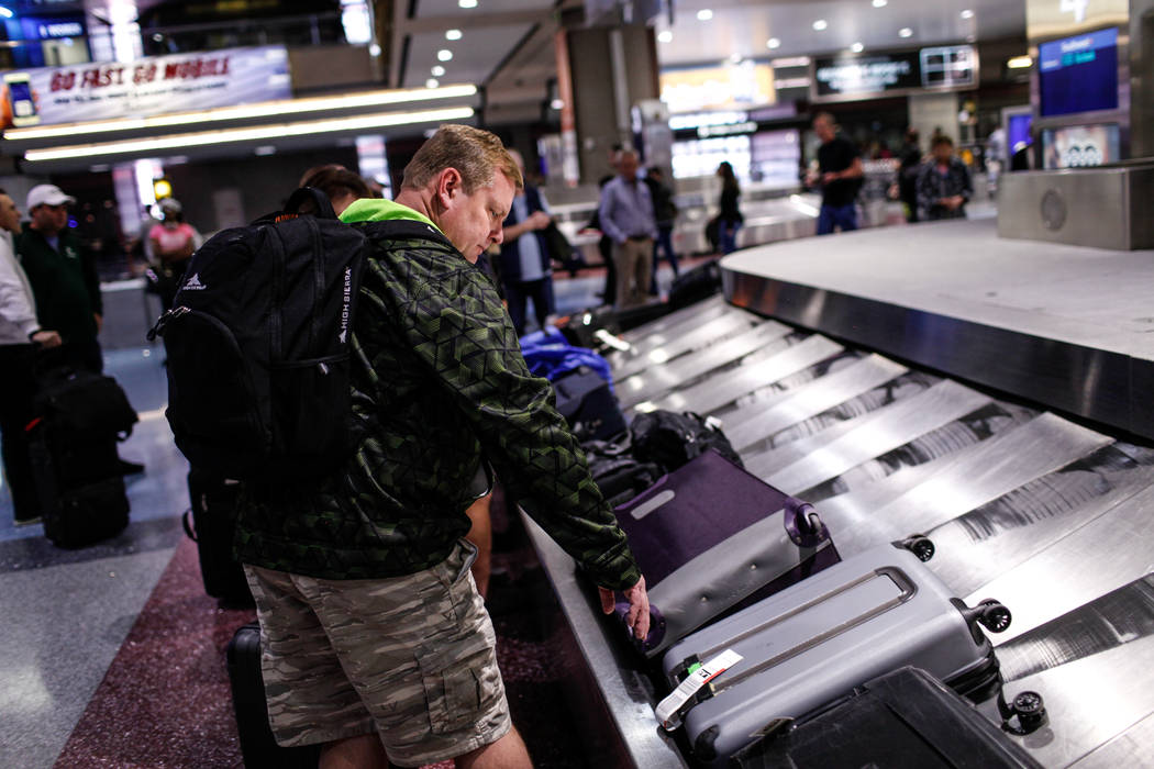 A man picks up his luggage at McCarran International Airport Terminal 1 baggage claim in Las Vegas, Friday, Oct. 13, 2017. Joel Angel Juarez Las Vegas Review-Journal @jajuarezphoto