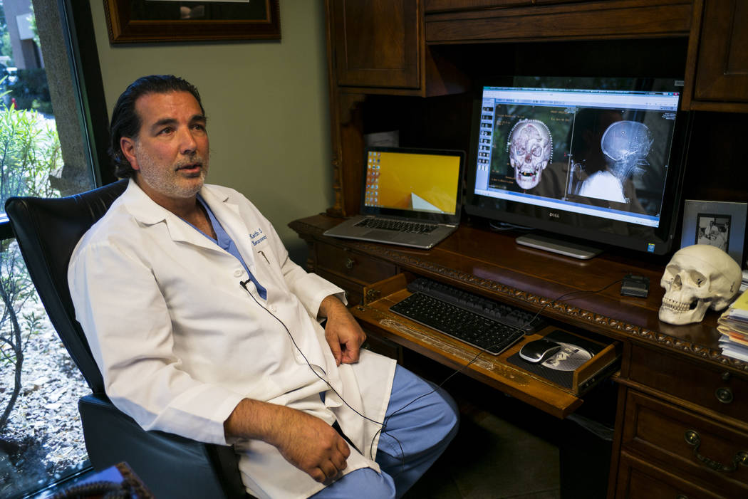 Dr. Keith Blum, a neurosurgeon who was on call at Sunrise Hospital and Medical Center the night of the mass shooting, looks at brain scans of patient Tina Frost at his office in Las Vegas on Wedne ...