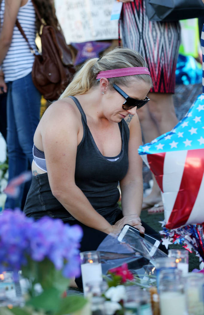 Las Vegas tourist from California Tanisha Borgstadt, grieves at a memorial across the street from the Mandalay Bay and the Route 91 Harvest Festival grounds in Las Vegas, Saturday, Oct. 7, 2017. B ...