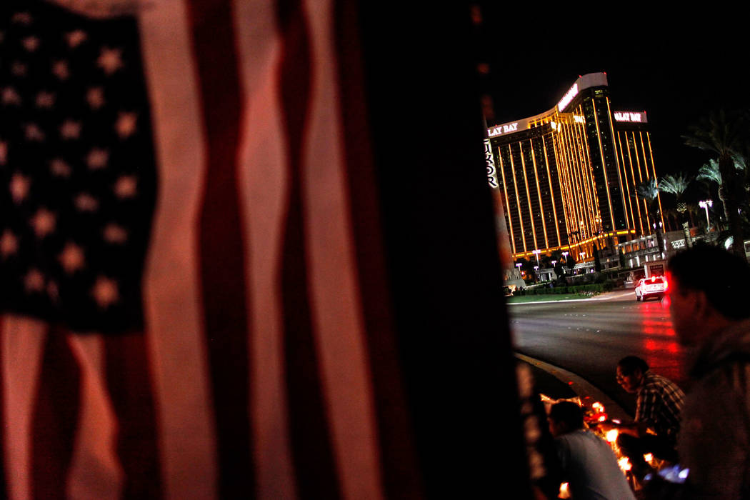 The Mandalay Bay is visible across from a vigil in remembrance of the mass shooting victims along The Strip in Las Vegas, Thursday, Oct. 5, 2017. The shooting on Sunday night killed 58 people and  ...
