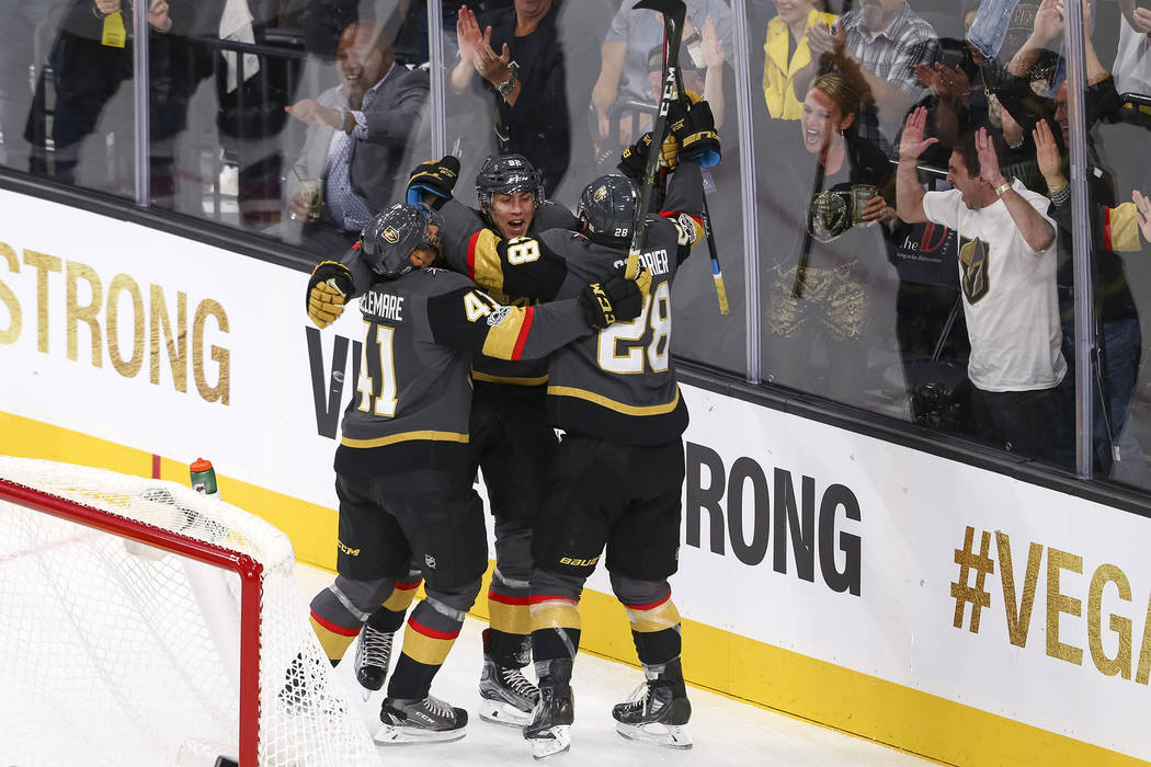 Vegas Golden Knights left wing Tomas Nosek (92) celebrates with Knights Pierre-Edouard Bellemare (41) and William Carrier (28) after scoring during the first period of an NHL hockey game between t ...