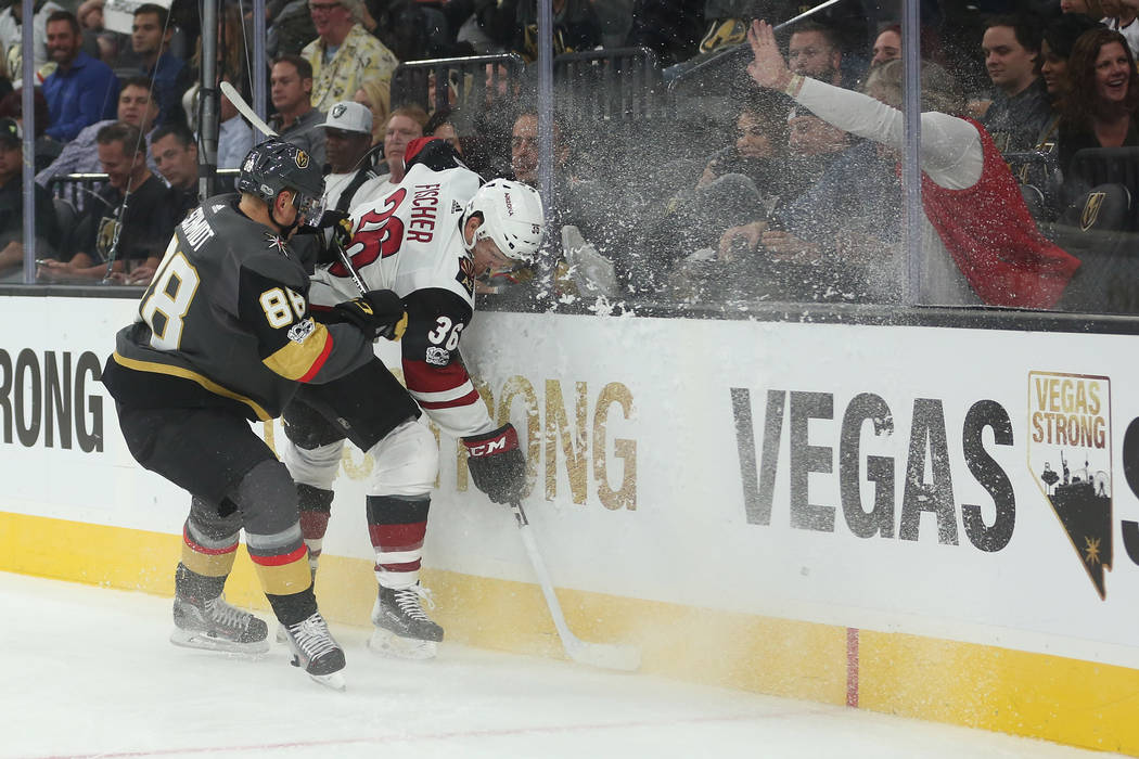 Vegas Golden Knights defenseman Nate Schmidt (88) checks Arizona Coyotes right wing Christian Fischer (36) into the glass during the third period against the Arizona Coyotes at T-Mobile Arena in L ...