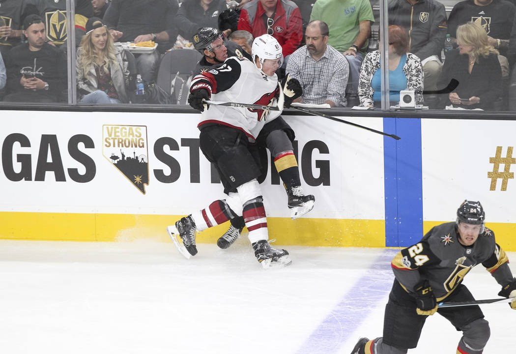 Vegas Golden Knights right wing Reilly Smith (19) is checked by Arizona Coyotes left wing Lawson Crouse (67) during the first period of an NHL hockey game between the Vegas Golden Knights and the  ...