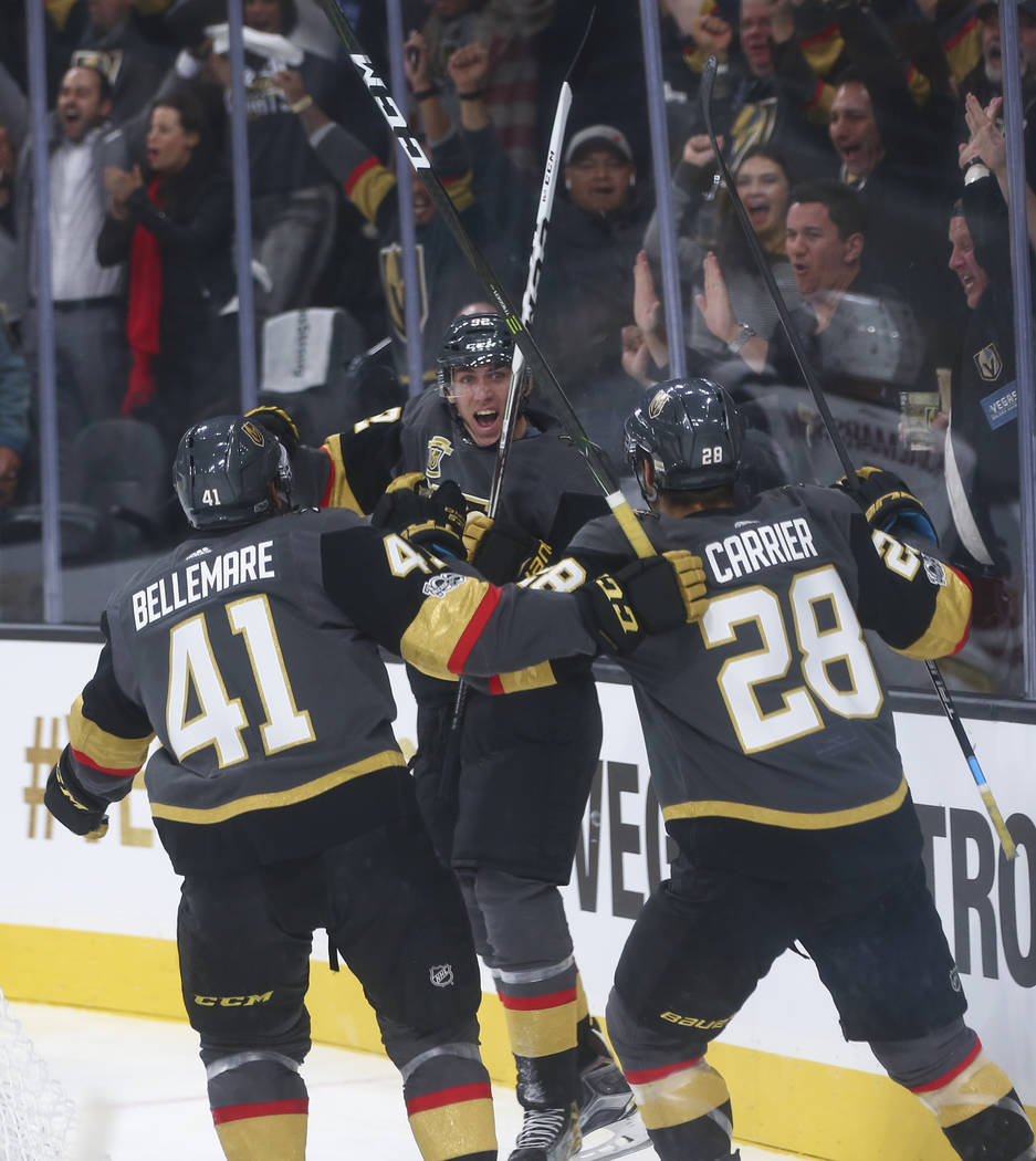 Vegas Golden Knights' Tomas Nosek (92) celebrates with Pierre-Edouard Bellemare (41) and William Carrier (28) after Nosek scored the first goal of the night against the Arizona Coyotes during an N ...