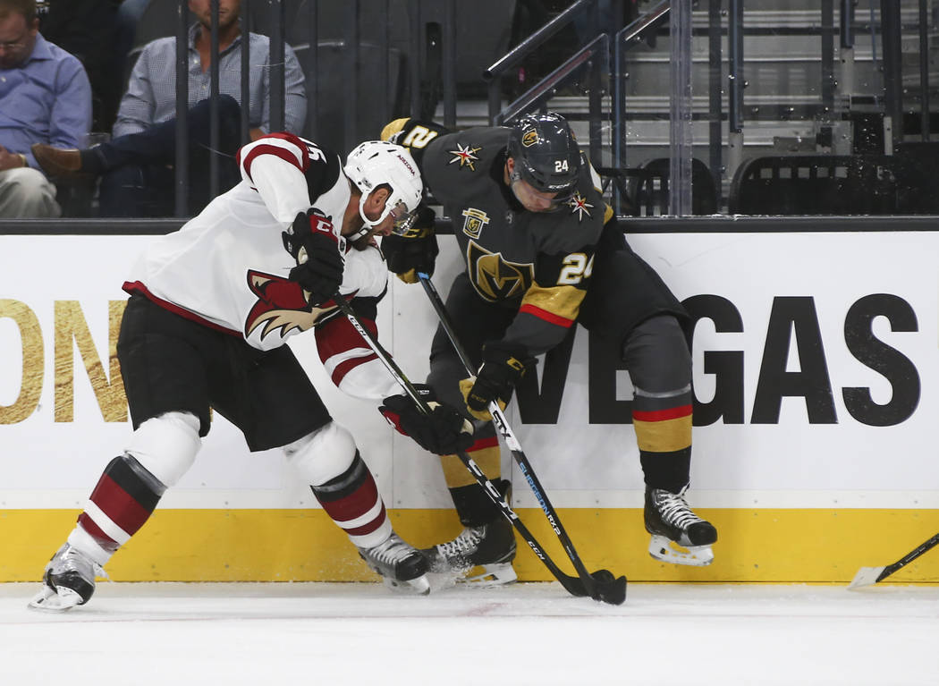 Vegas Golden Knights' Oscar Lindberg (24) and Arizona Coyotes' Brad Richardson (15) fight to control the puck during an NHL hockey game at T-Mobile Arena in Las Vegas on Tuesday, Oct. 10, 2017. Ch ...