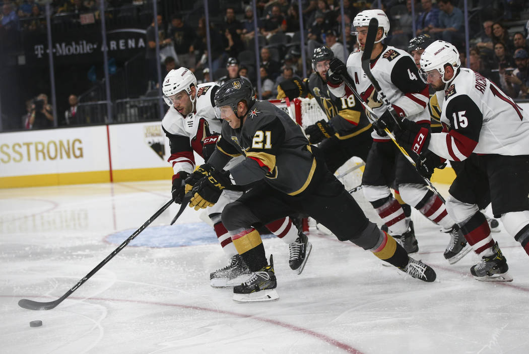 Vegas Golden Knights' Cody Eakin (21) chases down the puck against Arizona Coyotes' Jason Demers, left, during an NHL hockey game at T-Mobile Arena in Las Vegas on Tuesday, Oct. 10, 2017. The Gold ...