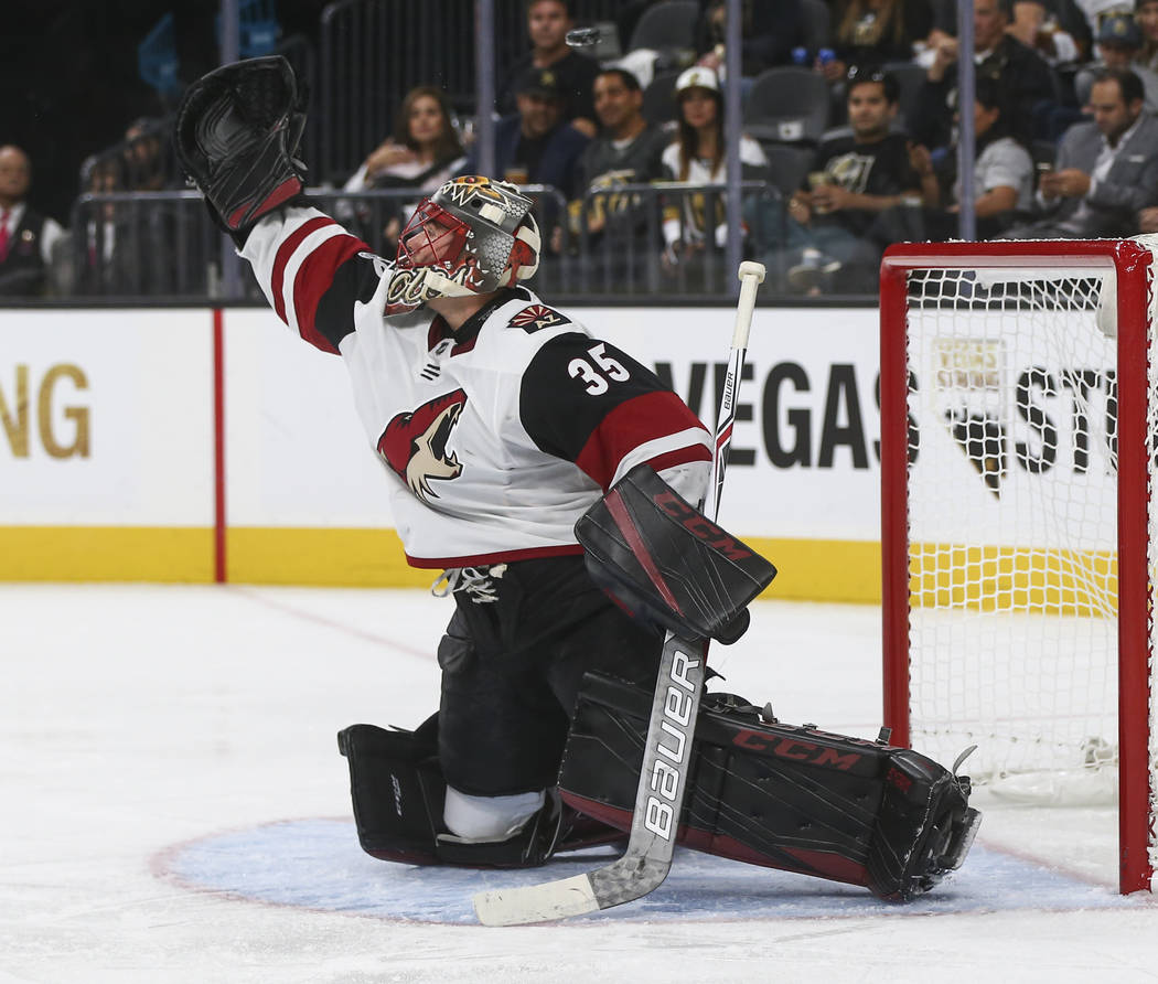 The puck flies above the head of Arizona Coyotes goalie Louis Domingue (35) during an NHL hockey game against the Vegas Golden Knights at T-Mobile Arena in Las Vegas on Tuesday, Oct. 10, 2017. The ...