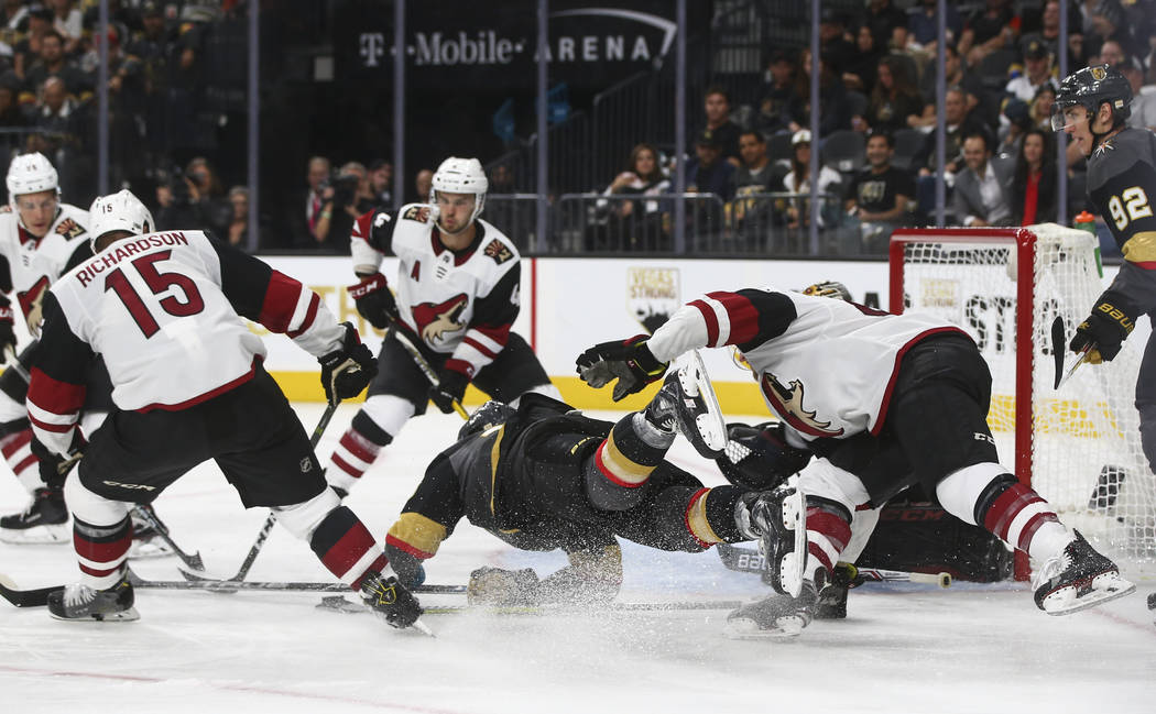 Vegas Golden Knights' William Carrier, center, is tripped up by Arizona Coyotes defenders during an NHL hockey game at T-Mobile Arena in Las Vegas on Tuesday, Oct. 10, 2017. The Golden Knights won ...