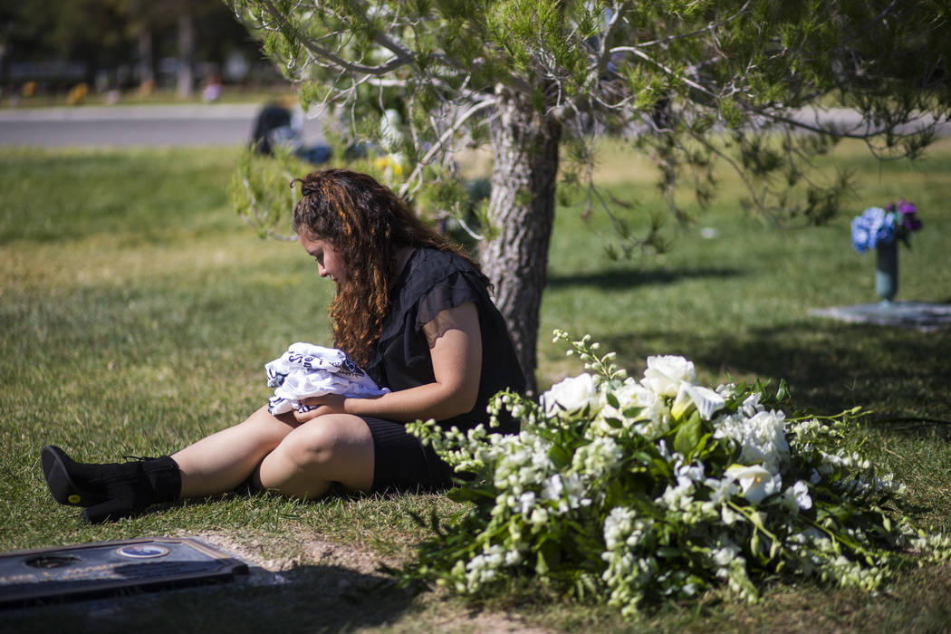 Sixteen-year-old Chantal Sosa rests next to the grave of her brother, Erick Silva, after his burial services at Davis Funeral Home & Memorial Park in Las Vegas on Thursday, Oct. 12, 2017. Silv ...