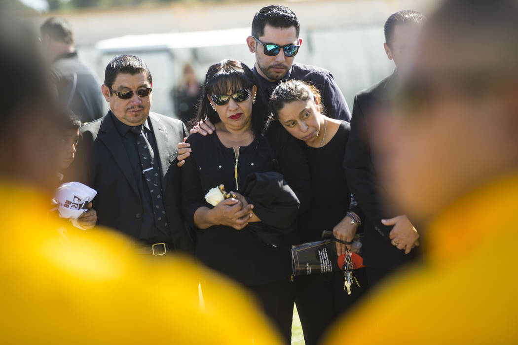Gregorio De La Rosa, left, and Angelica Cervantes, mother of Erick Silva, second from left, during funeral services for Silva at Davis Funeral Home & Memorial Park in Las Vegas on Thursday, Oc ...