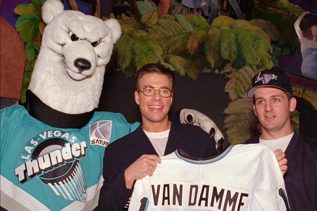 "Actor Jean-Claude Van Damme, center, is presented an honorary Las Vegas Thunder jersey by Greg Hawgood, right, captain of the minor-league hockey team, and team mascot ""Boom Boom"" during a stop at ..."