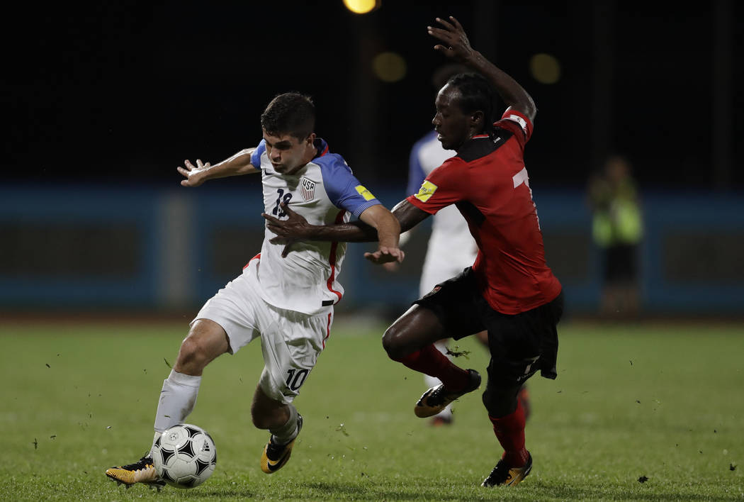 United States' Christian Pulisic, left, fight for the ball with Trinidad and Tobago's Nathan Lewis during a 2018 World Cup qualifying soccer match in Couva, Trinidad, Tuesday, Oct. 10, 2 ...