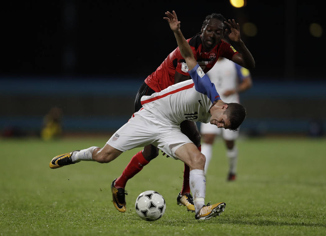 United States' Christian Pulisic, front, fights for control of the ball with Trinidad and Tobago's Nathan Lewis during a 2018 World Cup qualifyingsoccermatch in Couva, Trinidad, Tuesda ...