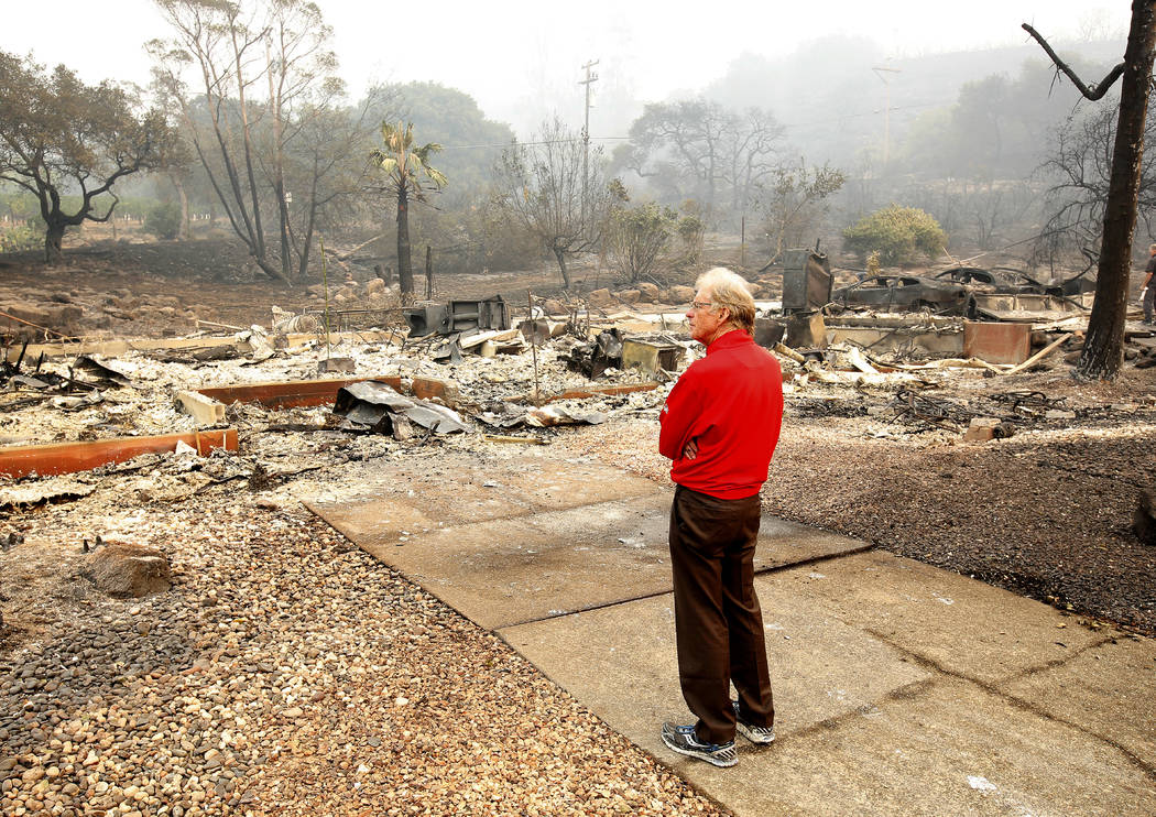 Mike Rippey looks over the burned out remains of his parents home at the Silverado Resort, Tuesday, Oct. 10, 2017, in Napa, Calif. Charles Rippey, 100 and his wife Sara, 98, died when wind whipped ...