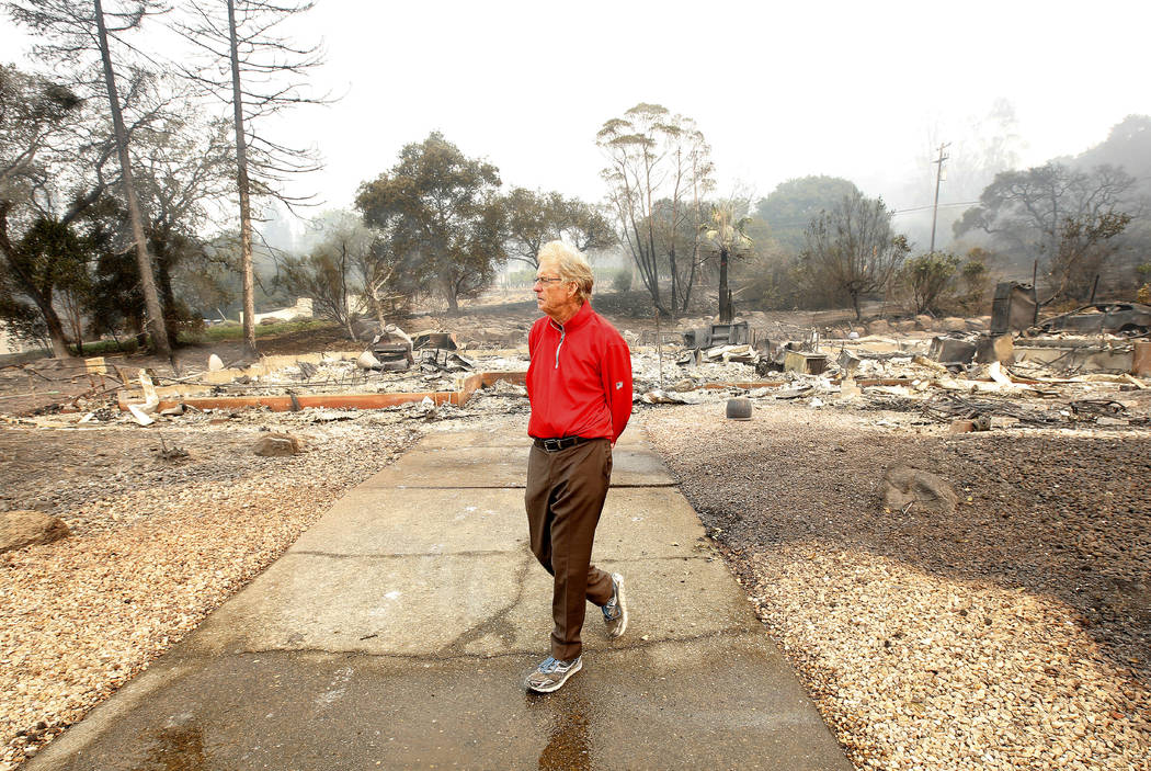 Mike Rippey walks away from the burned out remains of his parents home at the Silverado Resort, Tuesday, Oct. 10, 2017, in Napa, Calif. Charles Rippey, 100 and his wife Sara, 98, died when wind wh ...