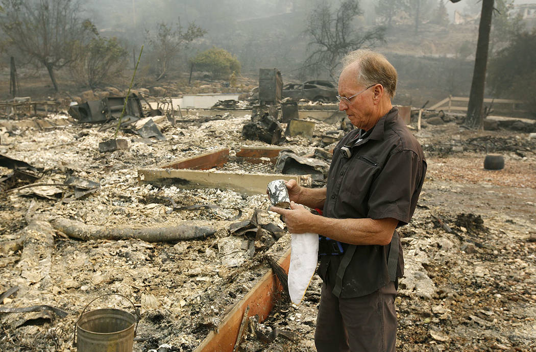 Chuck Rippey looks over a cup found in the burned out remains of his parent's home at the Silverado Resort, Tuesday, Oct. 10, 2017, in Napa, Calif. Charles Rippey, 100 and his wife Sara, 98, died  ...