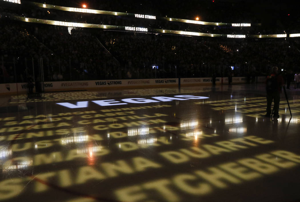 Names of victims in the mass shooting in Las Vegas are displayed on the ice before an NHL hockey game between the Vegas Golden Knights and Arizona Coyotes at T-Mobile Arena in Las Vegas on Tuesday ...