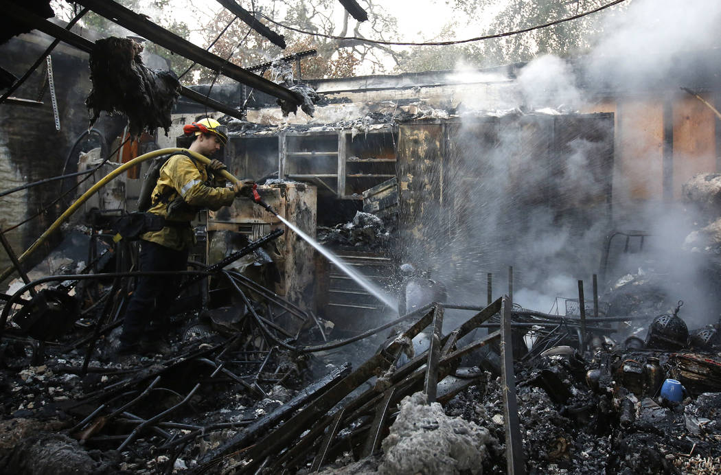 Firefighter Nick Gonzalez-Pomo, of the San Rafael Fire Department, waters down smoldering ashes on a garage Tuesday, Oct. 10, 2017, in Napa, Calif. Wildfires whipped by powerful winds swept throug ...