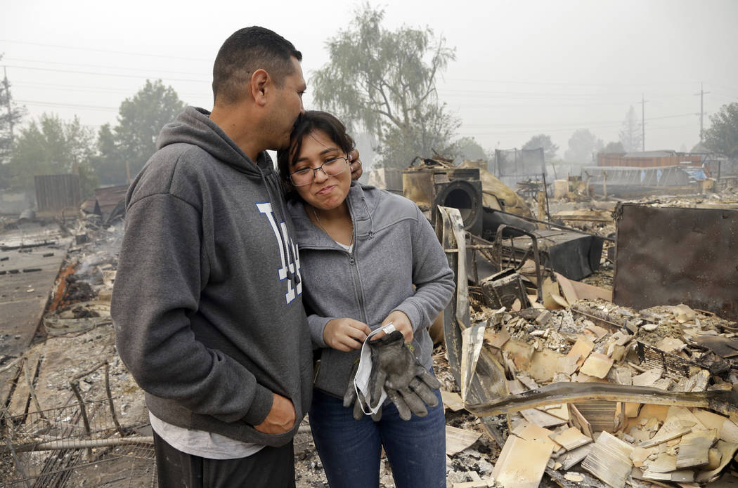 Jose Garnica, left, kisses his daughter Leslie Garnica in front of their home that was destroyed in the Coffey Park area of Santa Rosa, Calif., on Tuesday, Oct. 10, 2017. An onslaught of wildfires ...