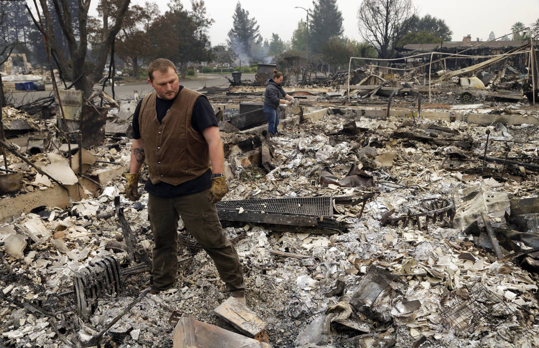 Luke Baier, left, and his wife Gina Baier look through the remains of their home in the Coffey Park area of Santa Rosa, Calif., on Tuesday, Oct. 10, 2017. An onslaught of wildfires across a wide s ...