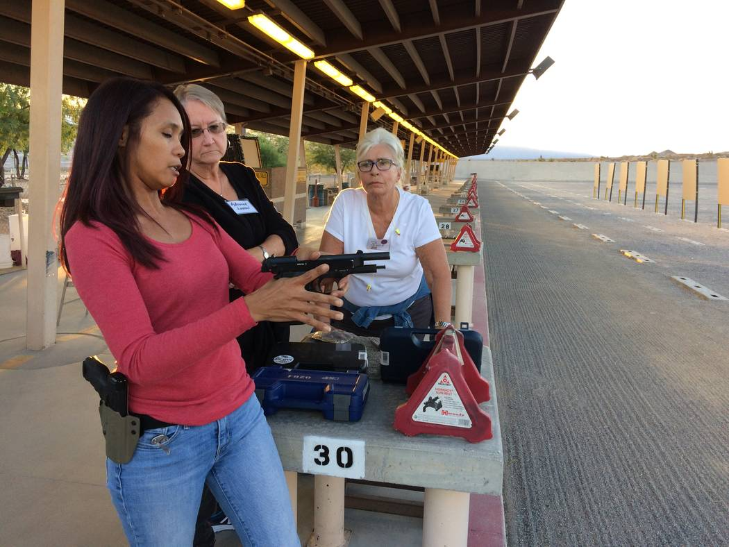 Jeannette Morgan, womens' program director at the Clark County Shooting Complex, talks about the features of a gun Oct. 10, 2017, as her fellow shooting coaches Adrienne Logan (center) and Ruth  ...