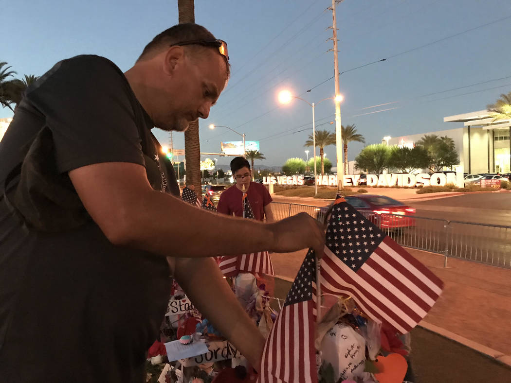 """Steve Round, 47, adjusts flags at a memorial site near the """"Welcome to Fabulous Las Vegas"""" sign on Wednesday, October 11, 2017. Blake Apgar Las Vegas Review-Journal @blakeapgar"""