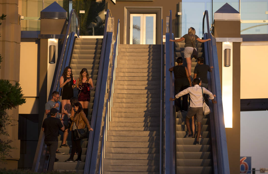 People take an escalator to cross a pedestrian bridge linking MGM Grand and Tropicana hotel-casino near the intersection of Las Vegas Boulevard and Tropicana Avenue in Las Vegas, Thursday, Oct. 12 ...