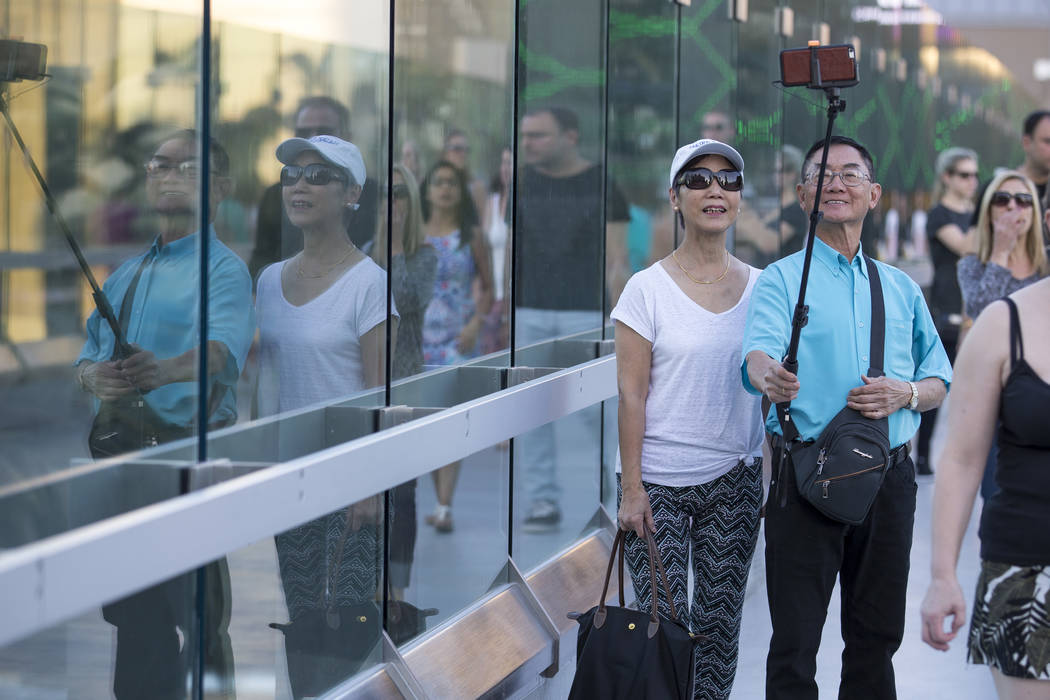A couple takes a selfie from a pedestrian bridge linking New York-New York and MGM Grand near the intersection of Las Vegas Boulevard and Tropicana Avenue in Las Vegas, Thursday, Oct. 12, 2017. Ri ...