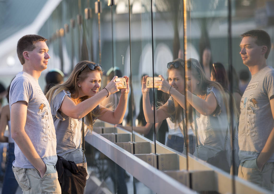 A woman snaps a photo from a pedestrian bridge linking MGM Grand and Tropicana hotel-casino near the intersection of Las Vegas Boulevard and Tropicana Avenue in Las Vegas, Thursday, Oct. 12, 2017. ...