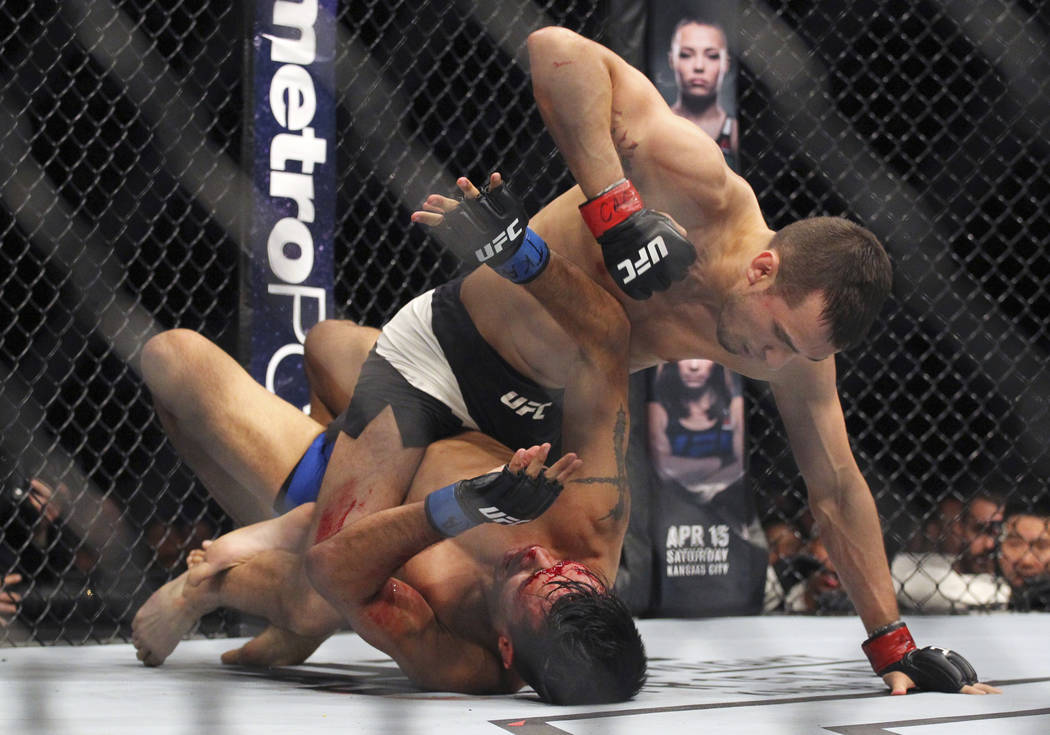Featherweight Myles Jury punches Mike De La Torre, bottom, during a mixed martial arts bout at UFC 210, Saturday, April 8, 2017, in Buffalo, N.Y. (AP Photo/Jeffrey T. Barnes)