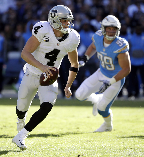 Oakland Raiders quarterback Derek Carr (4) scrambles away from San Diego Chargers defensive end Joey Bosa (99) during the first half of an NFL football game Sunday, Dec. 18, 2016, in San Diego. (A ...