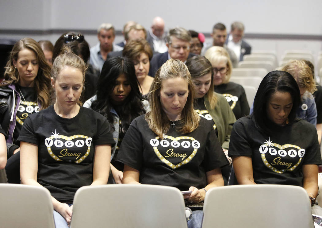 R&R Partners employees, incuding Cassidy Francois, front left, Lindsey Patterson and Yanick Dalhouse, right, bow their heads during prayer honoring the victims of the Route 91 Harvest festival ...