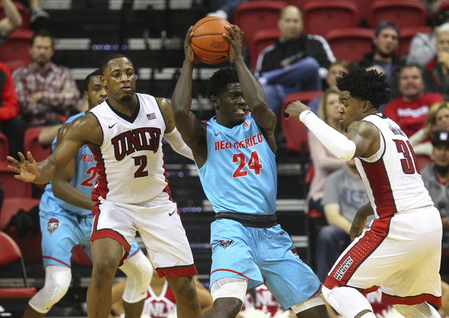 New Mexico guard Damien Jefferson (24) drives to the basket between UNLV guards Uche Ofoegbu (2) and Jovan Mooring (30) during a basketball game at the Thomas & Mack Center in Las Vegas on Wed ...