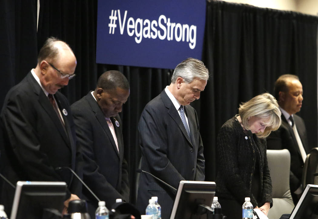 County Commissioner Lawrence Weekly, second left, Chuck Bowling, center, president and COO of the Mandalay Bay Resort and Casino and Kristin McMillan, second right, bow their heads during prayer d ...
