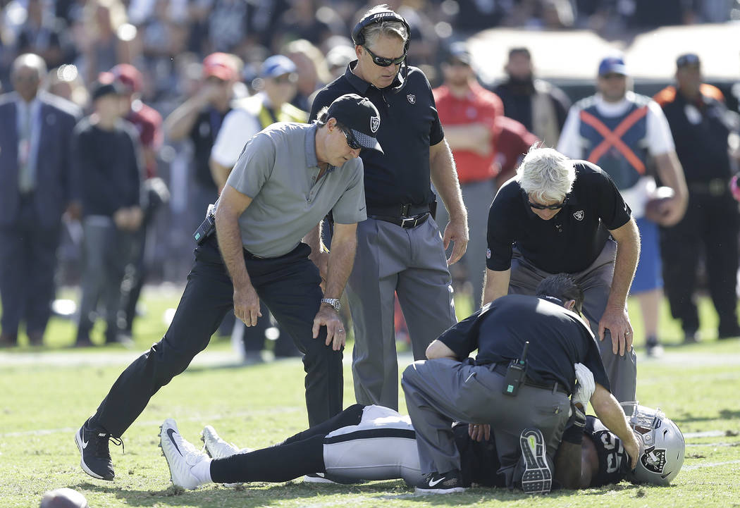 Oakland Raiders head coach Jack Del Rio, top, and trainers check on Oakland Raiders linebacker Marquel Lee during the second half of an NFL football game against the Baltimore Ravens in Oakland, C ...