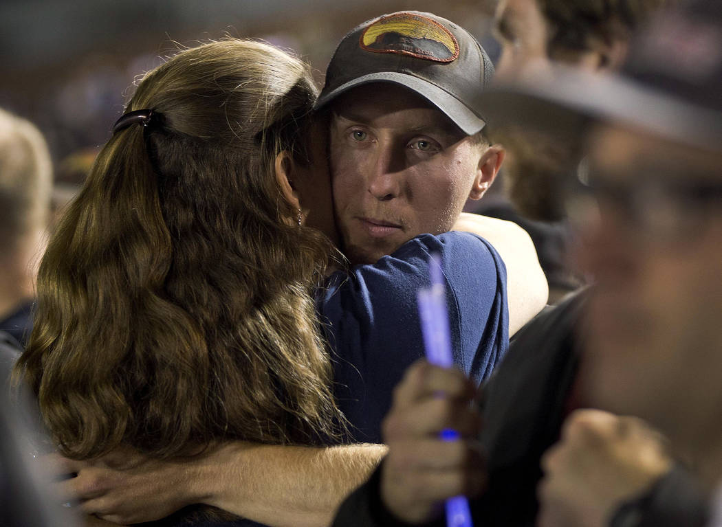 In this July 2, 2013, file photo, firefighter Brendan McDonough embraces a mourner near the end of a candlelight vigil in Prescott, Ariz. McDonough, the only member of an Arizona firefighting crew ...