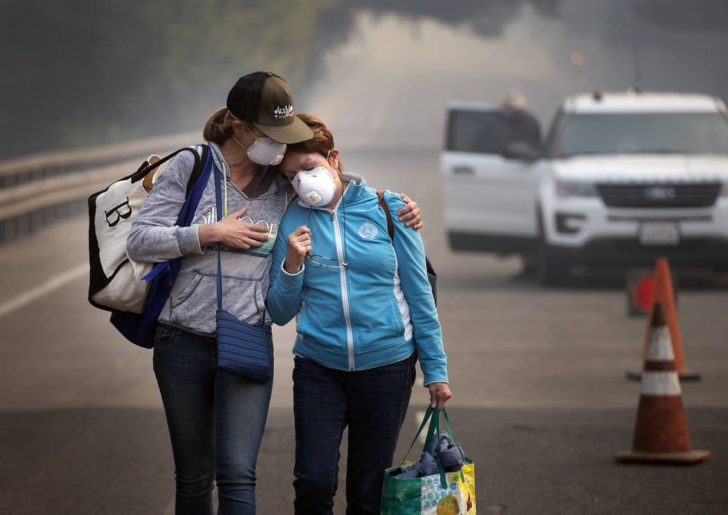 Colby Clark of San Francisco, left, comforts her mother, Bonnie Trexler, after being escorted by law enforcement to her home in Silverado Highland to retrieve medicine and some personal items on W ...